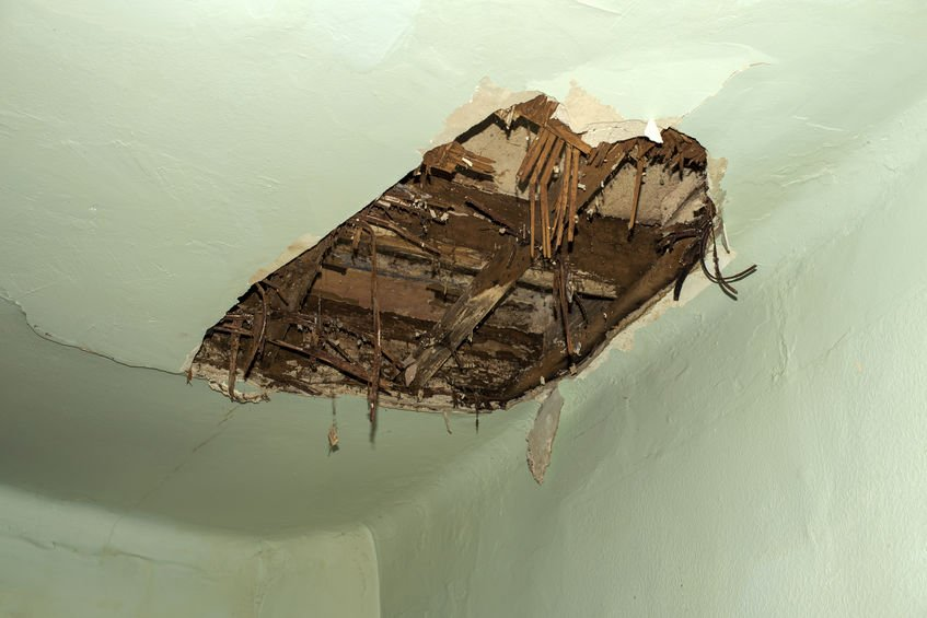 Roof damaged by water leakage with a large hole in the roof